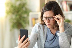 woman having trouble reading smartphone